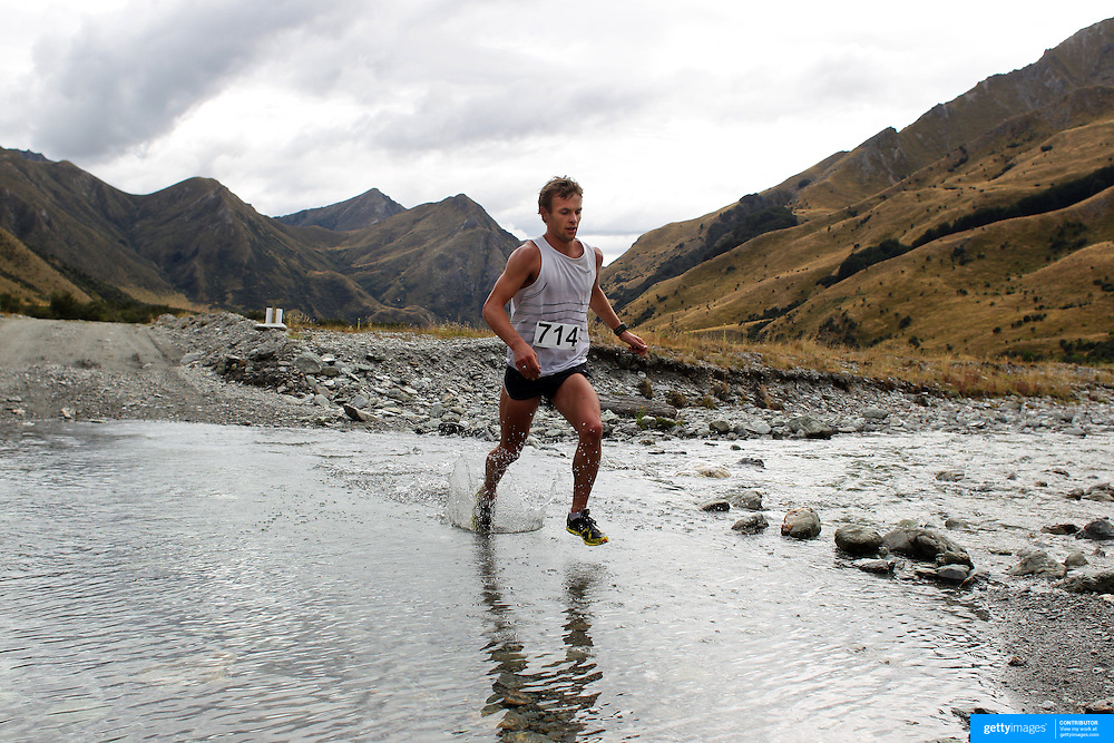Runner Oska Inkster-Baynes crosses  Moke Creek on the Ben Lomond High Country Station during the Pure South Shotover Moonlight Mountain Marathon and trail runs. Moke Lake, Queenstown, New Zealand. 4th February 2012. Photo Tim Clayton