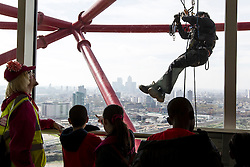 © Licensed to London News Pictures. 05/04/2014. Visitors look gaze through the window as a worker dangles 80 metres above East London preparing rigging for performing acrobats as part of the opening celebrations of the ArcelorMittal Orbit in Queen Elizabeth Park, Stratford. Photo credit : David Fearn/LNP