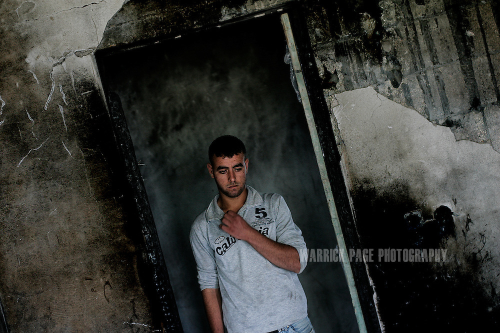 ATATRA, GAZA STRIP - JUNE 4: Omar Abu Halima stands in a charred doorway of his family home, June 4, 2009, in Atatra, Gaza Strip. Omar sufferes from sever shell-shock after watching four of his siblings and his father killed after a white phosphorus artillery strike burst through the ceiling of their home during the recent war in Gaza. Omar was shot in the arm by Israeli soldiers as he tried to evacuate wounded family members, while two of his cousins were shot dead beside him. Not since Fallujah or Grozny has white phosphorus been used so extensively in a civilian area. Phosphorus shells are legal to use as a battlefield obscurant in unpopulated areas, but are banned from use under the UN's Convention on Conventional Weapons (CCW) where civilians may be harmed. (Photo by Warrick Page)