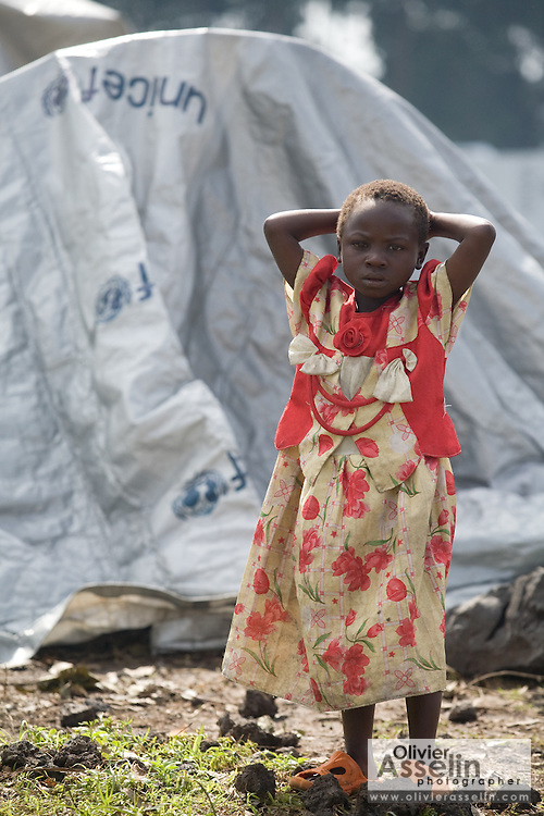 An internally displaced girls stands outside makeshift tents made of UNICEF-sponsored tarp at the Kibati IDP camp, on the outskirts of Goma, Eastern Democratic Republic of Congo on Friday December 12, 2008.