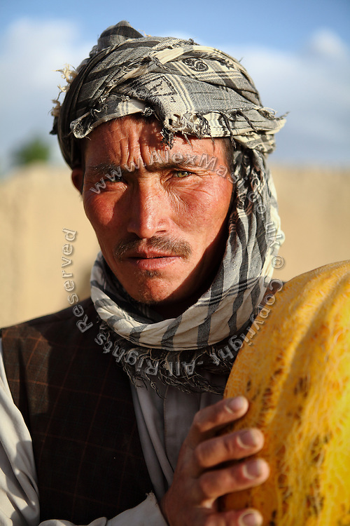 An Afghan man is carrying a papaya on the streets of Bamiyan's new bazaar. The cliff where once stood the Western Buddha (55m - 'Male') is photographed after sunset in Bamiyan, Afghanistan, an area mostly populated by Hazaras. The Buddhas of Bamiyan were two 6th century monumental statues of standing Buddhas carved into the side of a cliff in the Bamiyan valley in the Hazarajat region of central Afghanistan, situated 230 km northwest of Kabul at an altitude of 2500 meters. The statues represented the classic blended style of Gandhara art. The main bodies were hewn directly from the sandstone cliffs, but details were modelled in mud mixed with straw, coated with stucco. Amid widespread international condemnation, the smaller statues (55 and 39 meters respectively) were intentionally dynamited and destroyed in 2001 by the Taliban because they believed them to be un-Islamic idols. Once a stopping point along the Silk Road between China and the Middle East, researchers think Bamiyan was the site of monasteries housing as many as 5,000 monks during its peak as a Buddhist centre in the 6th and 7th centuries. It is now a UNESCO Heritage Site since 2003. Archaeologists from various countries across the world have been engaged in preservation, general maintenance around the site and renovation. Professor Tarzi, a notable An Afghan-born archaeologist from France, and a teacher in Strasbourg University, has been searching for a legendary 300m Sleeping Buddha statue in various sites between the original standing ones, as documented in the old account of a renowned Chinese scholar, Xuanzang, visiting the area in the 7th century. Professor Tarzi worked on projects to restore the other Bamiyan Buddhas in the late 1970s and has spent most of his career researching the existence of the missing giant Buddha in the valley.