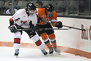 RIT's Darcy Henderson fights for a puck in the corner during an exhibition game at RIT's Gene Polisseni Center on Monday, September 29, 2014.