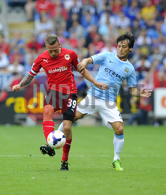 Cardiff City's Craig Bellamy battles for the ball with Manchester City's David Silva  - Photo mandatory by-line: Joe Meredith/JMP - Tel: Mobile: 07966 386802 25/08/2013 - SPORT - FOOTBALL - Cardiff City Stadium - Cardiff -  Cardiff City V Manchester City - Barclays Premier League