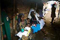 Recent mothers wait outside the home of a midwife in Mathare, a poor slum in Nairobi, Kenya.  Most women in Mathare can not afford to go to a hospital to give birth; they can not even afford the 10 minute taxi ride to get there.  The expecting mothers have no prenatal care and arrive to the midwives' homes once labor has already begun.  The midwives have no supplies and are usually have no formal training.  The mothers often give birth on dirt floors with no medicine, and their babies' unbilical cords are cut with dirty scissors and they are washed with tap water.