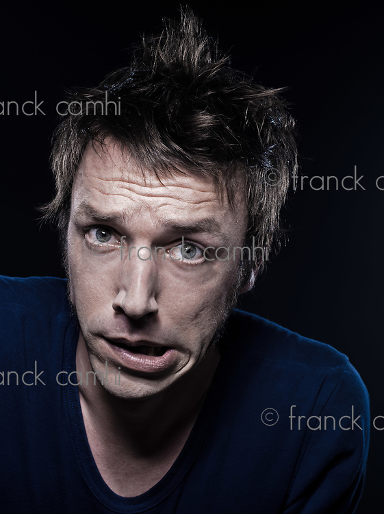 studio portrait on black background of a funny expressive caucasian man grimacing displeased