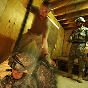 "CAMP LEMONIER, Djibouti -- 6/21/2006 -- U.S. Navy Quartermaster 1st Class Jonah Brixey guides a soldier from the 1/294 Guam Army National Guard Charlie Company through the trap door as part of a  ""Fast Rope"" training. Fast Roping is the process of sliding safely to the ground on a rope from a low-hovering helicopter. The indoor training environment gave the soldiers the chance to practice the needed skills through a trap door --  dropping ten feet to a padded floor. QM1 Brixey said, ""Most all of the guys picked it up pretty quick -- but I'm glad we did it here first."""