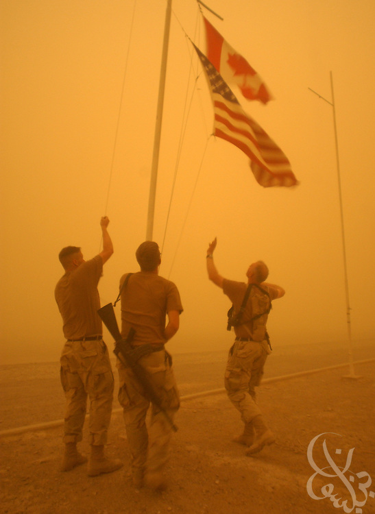 Members of the U.S. Army Alpha Company 2nd Batallion 187 regiment flag detail hastily lower American and coalition flags during a sudden dust storm May 13, 2002 at the Kandahar airfield in southern Afghanistan. U.S. and Coalition forces continue to occupy the airfield as part of Operation Enduring Freedom.