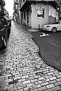 Cobblestoned street partly covered on asphalt