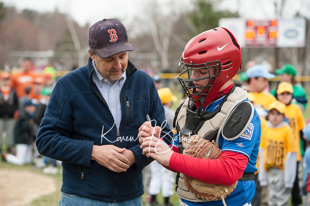 "Majors Rotary catcher Tyler Richter signs the ""first pitch"" ball for Mayor Ed Engler during Laconia Little League Opening Day festivities at Colby Field Saturday morning.   (Karen Bobotas/for the Laconia Daily Sun)"