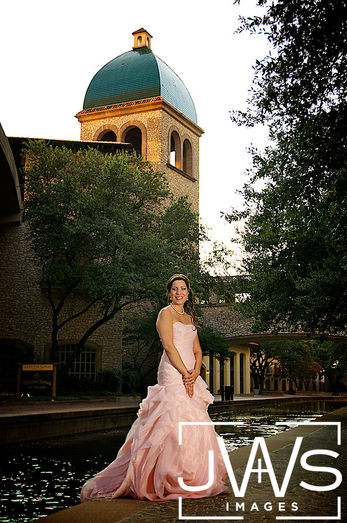 Bride standing in the Las Colinas Canals in pink wedding dress with the clock tower in the distance