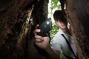 Costa Rican guide Ronald Jimenez photographs a greater sac-winged bat (Saccopteryx bilineata) through the narrow opening of a hollow 600 year old Almendro tree. Selva Verde Rainforest Reserve, Costa Rica.