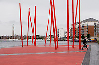 Grand Canal Square with red angled light sticks in Dublin's docklands Ireland, Ringsend power station chimneys in background