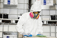 Technician in hazmat suit reading instructions on paper
