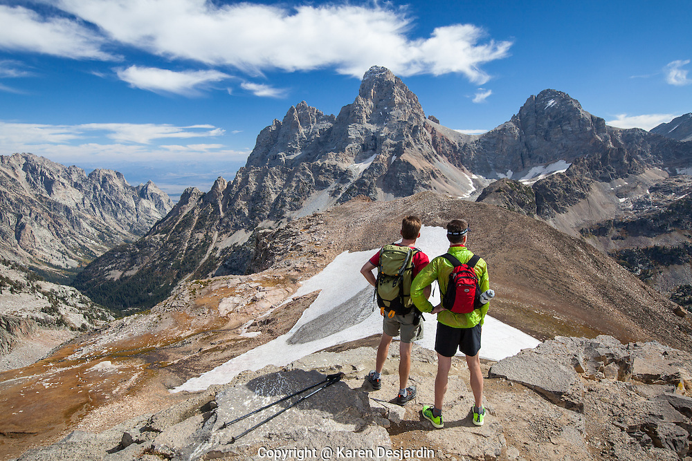 Two hikers at the top of Table Mountain, looking across to the Grand Teton in Teton National Park.