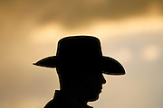 "061810-Evergreen, COLORADO-pbr-A bull rider is silhouetted by the sunset during the 3rd annual PBR ""Friday Night Bulls"" competition Friday, June 18, 2010 at the El Pinal Rodeo Grounds..Photo By Matthew Jonas/Evergreen Newspapers/Photo Editor"