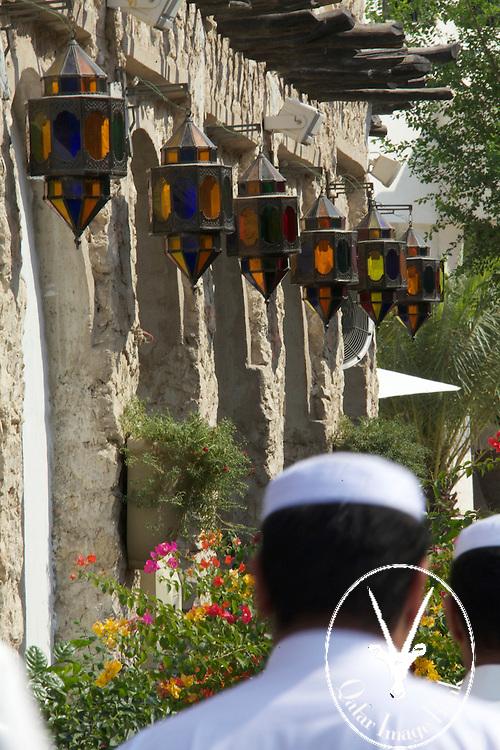 Men walking, colorful lamps overhead