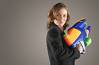 Smiling businesswoman standing holding water gun side view