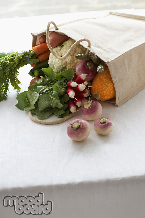 Bag full of fresh vegetables on table close-up
