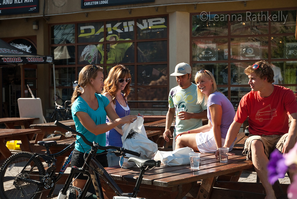 A group of young adults wait outside the Garbanzo Bike and Bean store in Whistler Village, BC.