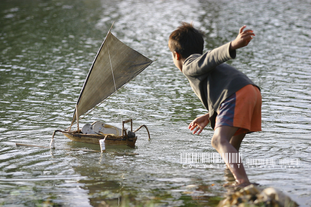 Un enfant de pêcheur joue avec son bateau. Bali.Indonésie. 2004.