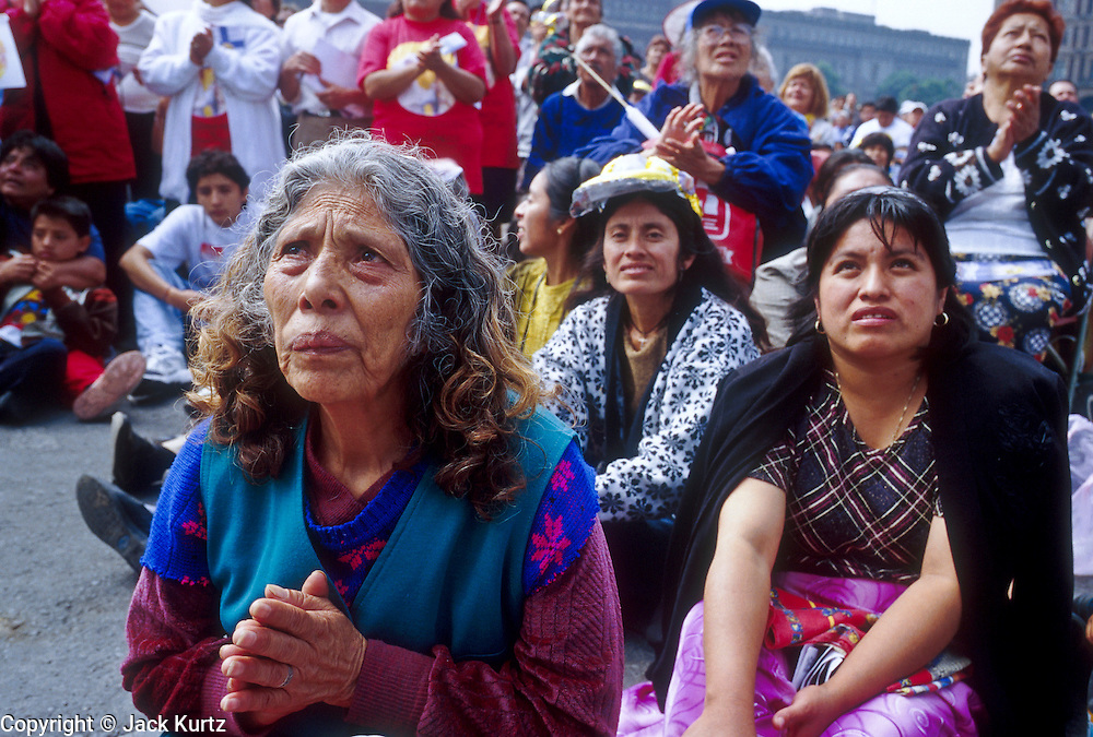 "jku032303051 - 31 JULY 2002 - MEXICO CITY, DF, MEXICO: People pray on the Zocalo in the historic center of Mexico City during a Papal mass televised to the Zocalo on large screen ""jumbotron"" televisions. The mass, led by Pope John Paul II, was at the Basilica of Guadalupe in Mexico City, July 31, 2002. The Pontiff, making his fifth trip to Mexico, canonized Juan Diego, the Mexican Indian who first saw the image of the Virgin of Guadalupe in 1531. Juan Diego is now known at Saint Juan Diego. PHOTO © JACK KURTZ  RELIGION  INDIGENOUS  CULTURE  PATRIOTISM"