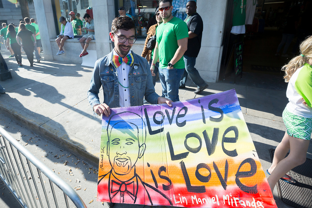 LBGTQ protester Clinton Edminster unfolds a sign near where Vice President Mike Pence will watch the Savannah St. Patrick's Day parade from a balcony at City Hall, Saturday, March 17, 2018, in Savannah, Ga. (AP Photo/Stephen B. Morton)