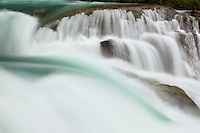 A small glacial waterfall is accentuated by a green flash of smooth running water. El Chalten, Argentina
