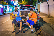 26 JULY 2013 - BANGKOK, THAILAND:     A food hawker sits in the back of his pickup truck with his son and plays guitar at the end of his work day on Sukhumvit Soi 18 in Bangkok, Thailand.  PHOTO BY JACK KURTZ