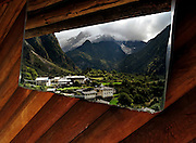 A guest-house bathroom mirror reflects Upper Yubeng village and the Meilie Xue Shan mountains.
