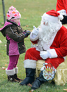 NEWTOWN, PA -  DECEMBER 7:  Chesney Schakenberg (L), 4, is greeted by Santa (played by fireman Justin Lewis) at Santa's annual Newtown Township Candy Cane hunt December 7, 2013 in Newtown, Pennsylvania. (Photo by William Thomas Cain/Cain Images)