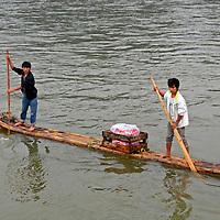 Asia, China, Guangxi, Guilin, Li River.  Life along the Li River involves locals paddling rafts to sell trinkets to visitors on passing cruiseboats.