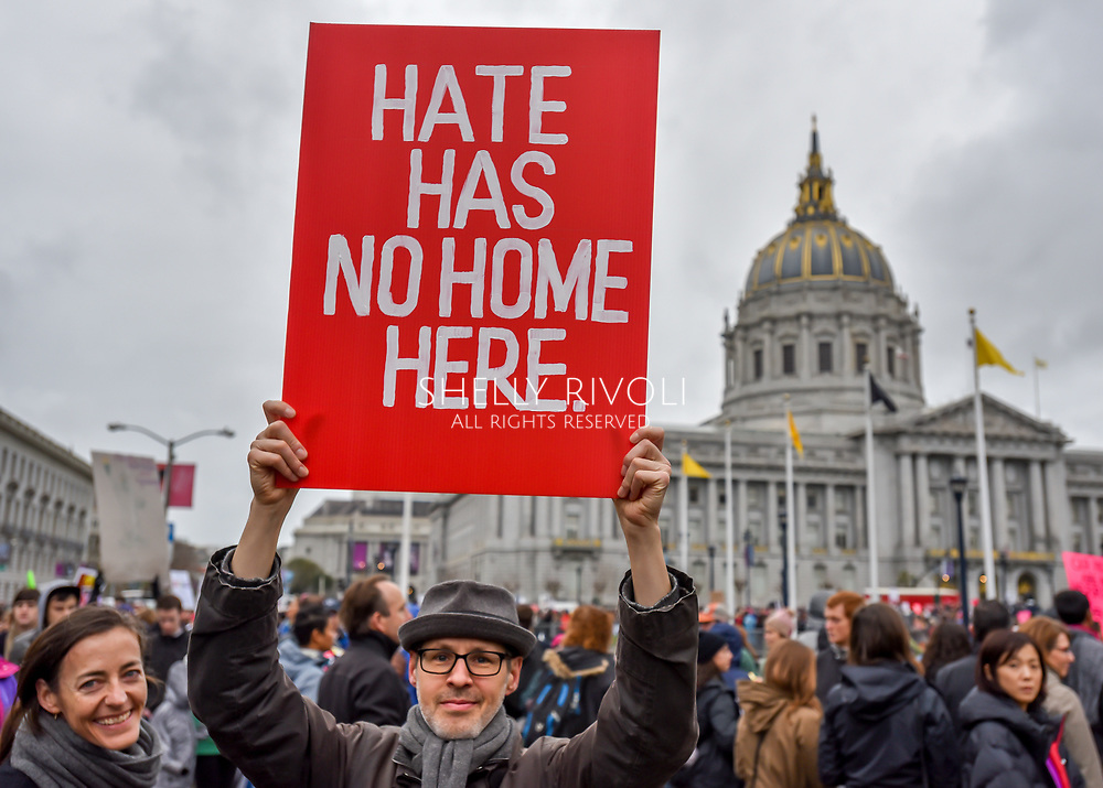 "In the crowd gathering at Civic Center Plaza before the Women's March, a man holds a bold red sign reading, ""Hate has no home here."""