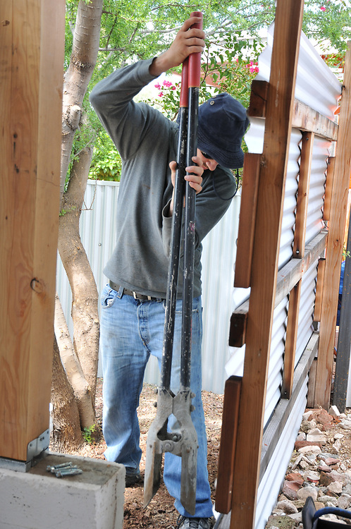Digging a fence post hole. This fence section will surround the still-open portion of my carport.