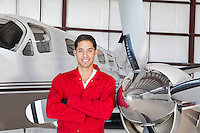 Portrait of young aeronautic engineer standing in front of airplane