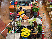 "11 AUGUST 2016 - BANGKOK, THAILAND: Flower sellers relax in Pak Khlong Talat in Bangkok. Pak Khlong Talat (literally ""the market at the mouth of the canal"") is the best known flower market in Thailand. It is the largest flower market in Bangkok. Most of the shop owners in the market sell wholesale to florist shops in Bangkok or to vendors who sell flower garlands, lotus buds and other floral supplies at the entrances to temples throughout Bangkok. There is also a fruit and produce market which specializes in fresh vegetables and fruit on the site. It is one of Bangkok's busiest markets and has become a popular tourist attraction.          PHOTO BY JACK KURTZ"