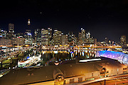 Darling Harbour at night. South Steyne former passenger ship serving as a function centre (l.), Sydney Tower and Centre.