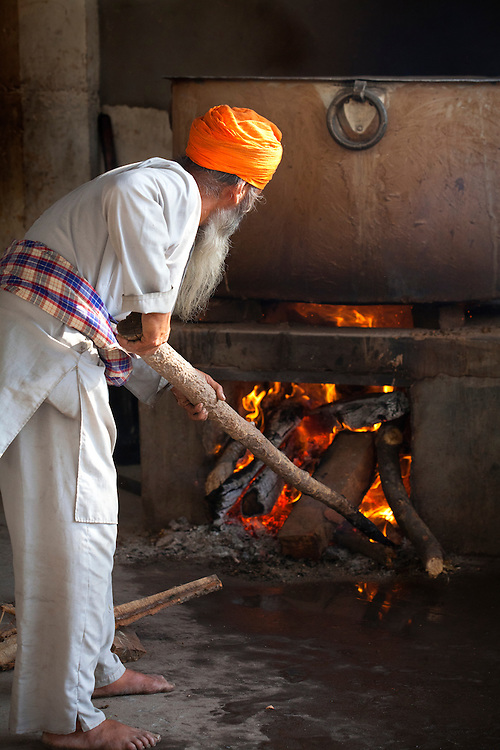 A Sikh cook builds a fire. The enormous pots are used to cook for the ten of thousands of visitors who come on a daily basis