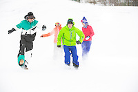 Full-length of young friends having fun in snow