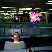Late at night, in a gloomy arrivals gate at Chicago O'Hare airport, a young man sits patiently on his own awaiting the arrival of his girlfriend after a holiday in Asia. It is the last flight to land and a helium balloon floats on a string bearing the words 'Welcome Home', a popular gesture for relatives in airports around the world, each having their own cultural way of showing affection for arriving family members after long absences. The balloon stands still, the only colour amid the drab interior of this sprawling airport hub. Picture from the 'Plane Pictures' project, a celebration of aviation aesthetics and flying culture, 100 years after the Wright brothers first 12 seconds/120 feet powered flight at Kitty Hawk,1903. .