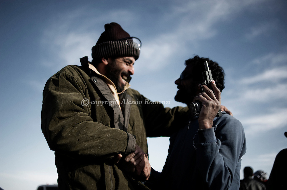 """LIBYA, BREGA : Anti Libyan government fighters shake their hands in the eastern town of Brega on March 13, 2011. Libyan state television said the town had been """"purged"""" of insurgents. ALESSIO ROMENZI"""
