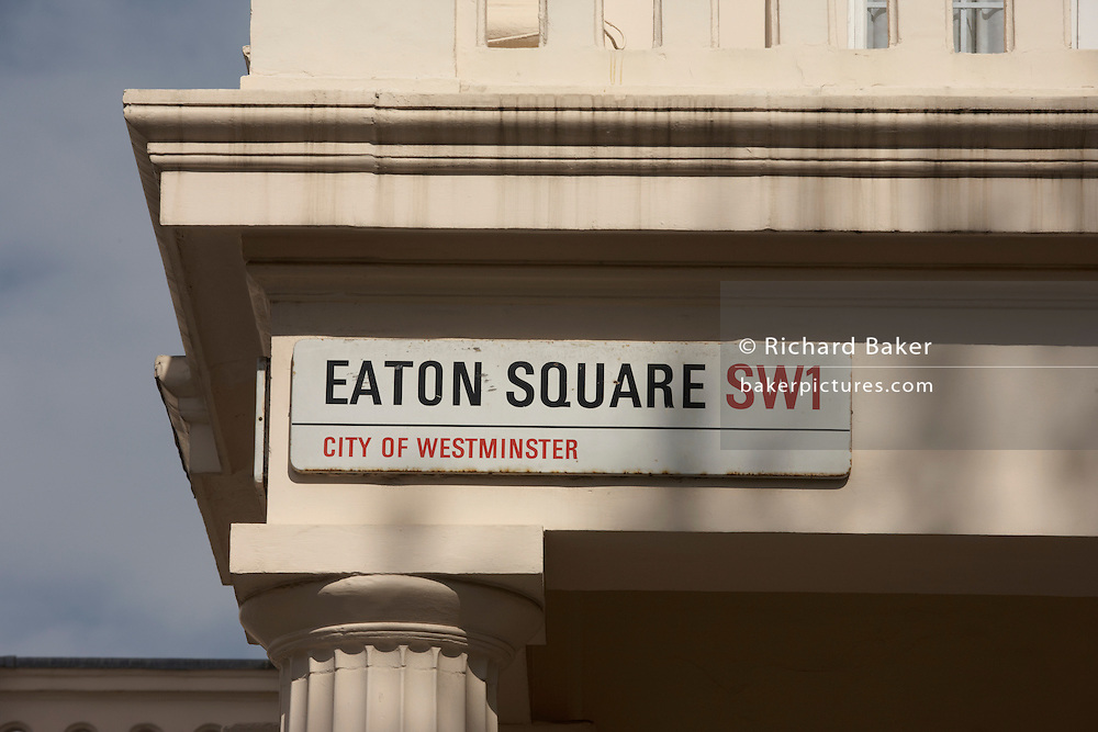 Detail of a City of Westminster sign describing this illustrious address in a wealthy part of London - Eaton Square. A single Doric column is seen lower-right and slightly discoloured paintwork from wet English weather is on the edge of the balcony of an otherwise exclusive and classically-designed street in Belgravia. Eaton Square is one of London's three garden squares built by Thomas Cubitt and the Grosvenor family when they developed the main part of Belgravia from 1826 until 1855. Belgravia attracts actors, politicians, ambassadors, big-budget bankers, traders and Prime Ministers like Neville Chamberlain and Stanley Baldwin at number 93.