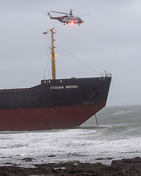 © Licensed to London News Pictures. 18/12/2018. Falmouth, UK. A search nd rescue helicopter flying over Russian cargo ship Kuzuma Minin, run aground on the reef off Gyllyngvase beach in Falmouth Bay in the early hours this morning. The Falmouth lifeboat and the Coastguard helicopter are involved in the major incident.  Photo credit: Mark Hemsworth/LNP
