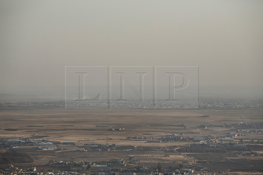 © Licensed to London News Pictures. 01/09/2015. Bashiqa, Iraq. Islamic State held territory, including Mosul, Iraq's second largest city, is seen from Kurdish peshmerga defensive positions on Bashiqa Mountain.<br /> <br /> Bashiqa Mountain, towering over the town of the same name, is now a heavily fortified front line. Kurdish peshmerga, having withdrawn to the mountain after the August 2014 ISIS offensive, now watch over Islamic State held territory from their sandbagged high-ground positions. Regular exchanges of fire take place between the Kurds and the Islamic militants with the occupied Iraqi city of Mosul forming the backdrop.<br /> <br /> The town of Bashiqa, a formerly mixed town that had a population of Yazidi, Kurd, Arab and Shabak, now lies empty apart from insurgents. Along with several other urban sprawls the town forms one of the gateways to Iraq's second largest city that will need to be dealt with should the Kurds be called to advance on Mosul. Photo credit: Matt Cetti-Roberts/LNP