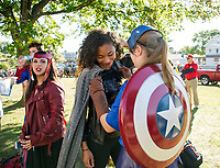 """Destiny Jones as """"Storm"""" gets her cape adjusted by """"Captain America"""" Katie Theberge as they prepare to march with the Junior class of Marvel Heroes during LHS Homecoming parade Friday afternoon.  (Karen Bobotas/for the Laconia Daily Sun)"""