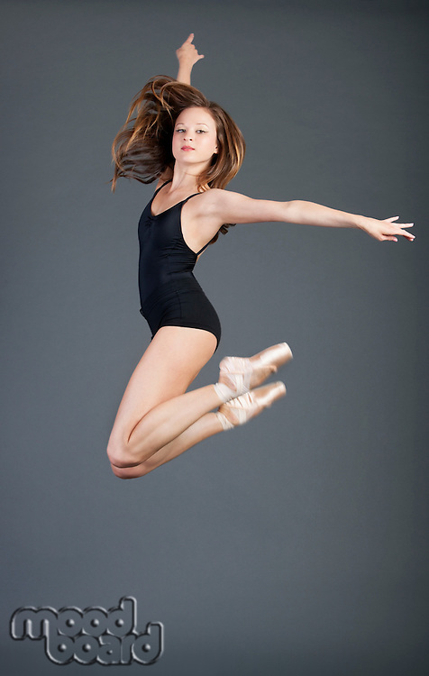 Portrait of young ballet dancer in mid-air over grey background