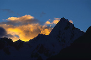 Alpamayo peak (19,500 feet elevation) soars above the Santa Cruz Trek at sunset in Huascaran National Park, Cordillera Blanca, Andes Mountains, Peru, South America. UNESCO honored Huascaran National Park on the World Heritage List in 1985. The Cordillera Blanca mountain range is in the Sierra Central of the Peruvian Andes.