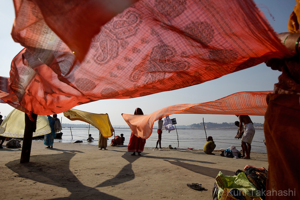 Women hold sarees to dry them during Kumbh Mela in Allahabad in India on Feb 8, 2013. Up to100 million worshippers gather over 55 days of the biggest Hindu religious event in the world to take a ritual bath in the holy waters, believed to cleanse sins and bestow blessings. <br /> (Photo by Kuni Takahashi)