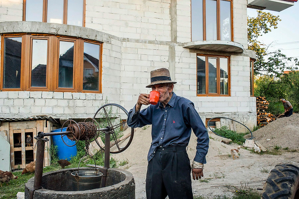 Iacob Berende drinks a cup of water from the well behind his children's newly built home which is still under construction. His children have gone to the UK to work. Most people from this village used to be animal breeders but now the younger generation has left and gone abroad to work.
