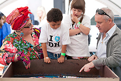 © Licensed to London News Pictures. 14/06/2012. LONDON, UK. Artist Damien Hirst (R) and  Kids Company founder Camilla Batmanghelidjh (L) supervise two children as they create artwork in Covent Garden, London, today (14/06/12). In celebration of Damien Hirst's current exhibition at the Tate Modern, the artist held a pubic art event giving British School children the chance to create their own versions of his iconic spin paintings. Photo credit: Matt Cetti-Roberts/LNP