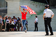 Julio Diaz, 28, of Chicago, IL, runs down the steps of the Supreme Court in celebration after the Court ruled 5-4 to strike down the Defense of Marriage Act.